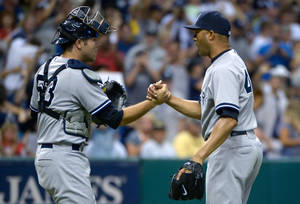 Photo - New York Yankees reliever Mariano Rivera, right, is congratulated by catcher Austin Romine after getting the save in a 3-2 victory over the Tampa Bay Rays in a baseball game in St. Petersburg, Fla., Sunday, Aug. 25, 2013. (AP Photo/Phelan M. Ebenhack)