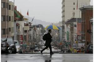 Photo - A man crosses Stockton Street in San Francisco, Wednesday, Feb. 26. Photo by Jeff Chiu / AP
