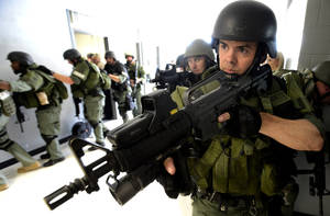 Photo - Jefferson County SWAT team members move down a hallway during an active shooter training exercise at a school in Ketona, Ala., Wednesday, June 18, 2014.  The exercise involved hostage negotiators, bomb squad and the SWAT team.  (AP Photo/ AL.com, Mark Almond) MAGS OUT