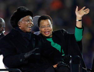 Photo - FILE - In this July 11, 2010 file photo, former South African President Nelson Mandela, left, sits next to his wife, Graca Machel, as they are driven across the field ahead of the World Cup final soccer match between the Netherlands and Spain at Soccer City in Johannesburg, South Africa.   South Africa's president Jacob Zuma says, Thursday, Dec. 5, 2013, that Mandela has died. He was 95.  (AP Photo/Luca Bruno, File)