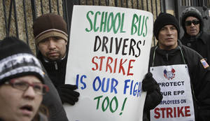 photo - FILE- In this Jan. 17, 2013 file photo, striking school bus drivers walk a picket line outside the Atlantic Express school bus facility in the Queens borough of New York.  Leaders of school bus drivers' union, Local 1181 of the Amalgamated Transit Union, are ending their month long strike in New York City, Friday, Feb. 15, 2013. The strike was suspended a day after five Democratic mayoral candidates sent a letter to the union asking drivers to return to work, promising that if elected, they will revisit the job security issue fueling the strike.  (AP Photo/Bebeto Matthews, File)
