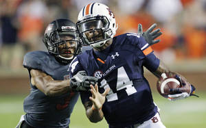 Photo - Auburn quarterback Nick Marshall (14) is chased down on a first down run by Arkansas State defensive back Raziel Valgis (3) in the first half of an NCAA college football game in Auburn, Ala., Saturday, Sept. 7, 2013. (AP Photo/Jay Sailors)
