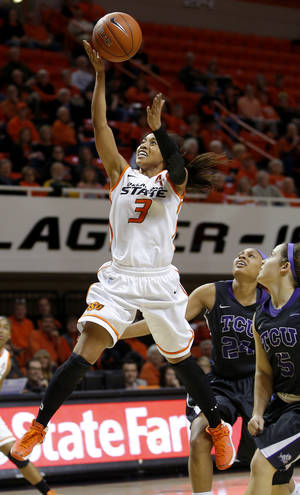 Photo - OSU's Tiffany Bias scores past TCU's Natalie Ventress, center, and Meagan Henson, right, during a Cowgirls' win last week. Photo by Bryan Terry, The Oklahoman