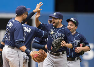 Photo - Tampa Bay Rays James Loney, left, Matt Joyce, center, and Sam Fuld, right, celebrate after the Rays defeated the Toronto Blue Jays 7-6 in a baseball game in Toronto on Sunday, Sept. 29, 2013. (AP Photo/The Canadian Press, Frank Gunn)