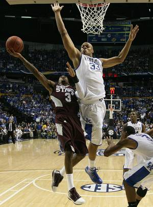Photo - Kentucky's Daniel Orton (33) defends against the shot of Mississippi State's Dee Bost (3) in the second half of an NCAA college basketball game on Sunday, March 14, 2010, at the Southeastern Conference tournament in Nashville, Tenn. (AP Photo/Dave Martin)