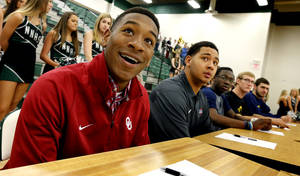 Photo - Football signees Nick Basquine, University of Oklahoma walk-on, and  Payton Prince, Tulsa University sit at a table during signing day ceremonies at Norman North High School on Wednesday, Feb. 5, 2014 in Norman, Okla.  Photo by Steve Sisney, The Oklahoman