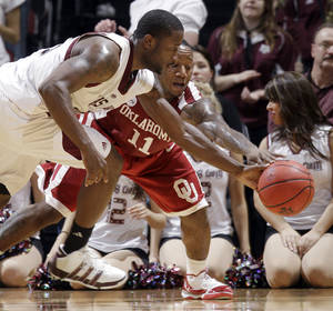 Photo - Oklahoma's Tommy Mason-Griffin (11) tries to steal the ball from Texas A&M's Donald Sloan, left, during the first half of an NCAA college basketball game Tuesday, Jan. 19, 2010, in College Station, Texas. AP PHOTO