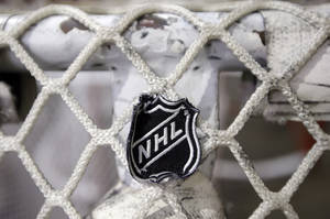 Photo - FILE - In this file photo taken Sept. 17, 2012, the NHL logo is seen on a goal at a Nashville Predators practice rink in Nashville, Tenn. The NHL eliminated 16 more days from the regular-season schedule Monday, Dec. 10, 2012, and if a deal with the players' association isn't reached soon the whole season could be lost. The league wiped out all games through Dec. 30 in its latest round of cancellations. Negotiations between the league and the players' association broke off last week, but NHL deputy commissioner Bill Daly said Sunday the sides are trying to restart talks this week. (AP Photo/Mark Humphrey, file)