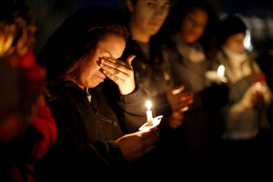 Photo - Chellie Fernandez becomes emotional as she speaks during the vigil Tuesday at OU.