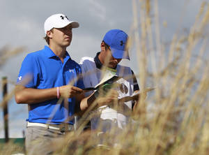 Photo - FILE - In this July 18, 2013, file photo, Jordan Spieth, of the United States, prepares to play off the 18th tee with his caddie during the first round of the British Open Golf Championship at Muirfield, Scotland. Last year,  he showed up as a 19-year-old fresh off his first win, and the kid who left Texas after one year and no guarantees is now talked about as a favorite at every major he plays. (AP Photo/Peter Morrison, File)