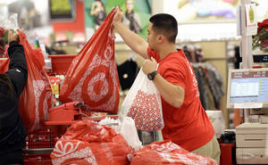 Photo - A Target employee hands bags to a customer at the register at a Target store in Colma, Calif. Target's fiscal fourth-quarter net income dipped 2 percent as it dealt with intense competition during the crucial holiday season. AP Photo <strong>Jeff Chiu</strong>