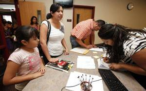 Photo - Elementary Clerk Claribel Barron (right) assists seven year old Hidy Ortiz and her mother Erica Balderas with Hidy's enrollment in classes at the new Cesar Chavez Elementary School. PHOTO BY Paul Hellstern, The Oklahoman <strong>PAUL HELLSTERN</strong>