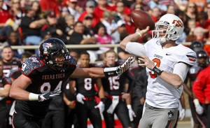 Photo - Oklahoma State quarterback Brandon Weeden (3) passes under pressure from Texas Tech defender Scott Smith, left, in the second quarter of an NCAA college football game in Lubbock, Texas, Saturday, Nov. 12, 2011. (AP Photo/Sue Ogrocki) ORG XMIT: TXSO107
