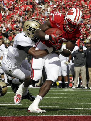 Photo - Wisconsin's Melvin Gordon (25) breaks away from Purdue's Taylor Richards for a touchdown run during the first half of an NCAA college football game Saturday, Sept. 21, 2013, in Madison, Wis. (AP Photo/Morry Gash)