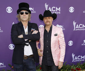 "Photo -   FILE - This April 1, 1012 file photo shows Big Kenny, left, John Rich, of musical group Big and Rich, arriving at the 47th Annual Academy of Country Music Awards in Las Vegas. After a five-year break, Big & Rich are putting the funny back in country music _ with the help of Jon Bon Jovi and Richie Sambora.The unlikely quartet gathered to write two songs for the country duo's new album ""Hillbilly Jedi"" after they struck up a friendship a few years back. (AP Photo/Isaac Brekken, file)"