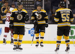 Photo - Boston Bruins' Jarome Iginla, left, goes to congratulate teammate Johnny Boychuk (55) after Iginla's goal against the Phoenix Coyotes as Milan Lucic looks on during the first period of an NHL hockey game in Boston Thursday, March 13, 2014. (AP Photo/Winslow Townson)