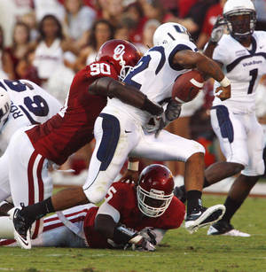 Photo - David King (90) causes a fumble by Diondre Borel (12) during the first half of the college football game between the University of Oklahoma Sooners (OU) and Utah State University Aggies (USU) at the Gaylord Family-Oklahoma Memorial Stadium on Saturday, Sept. 4, 2010, in Norman, Okla.   Photo by Steve Sisney, The Oklahoman