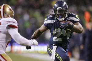 Photo - Seattle Seahawks' Marshawn Lynch (24) rushes against the San Francisco 49ers in the first half of an NFL football game, Sunday, Dec. 23, 2012, in Seattle. (AP Photo/Elaine Thompson)