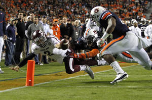 photo -   Texas A&M quarterback Johnny Manziel (2) dives for the end zone for a touchdown past Auburn linebacker Cassanova McKinzy (30) and Auburn linebacker Daren Bates (25) during the first half of an NCAA college football game on Saturday, Oct. 27, 2012, in Auburn, Ala. (AP Photo/Butch Dill)