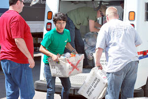 Photo - Volunteers unload donated food from a postal truck during last year's Stamp Out Hunger food drive. Photo provided by Regional Food Bank of Oklahoma. <strong></strong>
