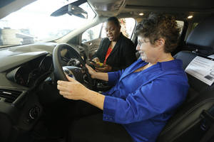 Photo - Carol Fletcher-Knight, left, and Bettie Shadoan examine a Ford Escape Tuesday in Oklahoma City that they could win if they are named Oklahoma City Teacher of the Year. Photo By Steve Gooch, The Oklahoman <strong>Steve Gooch</strong>