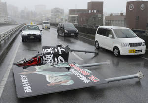 Photo -   An advertising billboard blown away by wind lies on a road in Naha as Typhoon Jelawat hit the southern Japanese prefecture of Okinawa Saturday, Sept. 29, 2012. (AP Photo/Kyodo News) JAPAN OUT, MANDATORY CREDIT, NO LICENSING IN CHINA, FRANCE, HONG KONG, JAPAN AND SOUTH KOREA