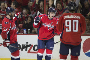 Photo - Washington Capitals defenseman Dmitry Orlov, center, celebrates his first-period goal against the Philadelphia Flyers with teammates defenseman Mike Green, left, and center Marcus Johansson, Sunday, March 2, 2014, in Washington. (AP Photo/ Evan Vucci)
