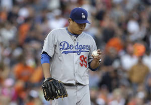 Photo - Los Angeles Dodgers pitcher Hyun-Jin Ryu looks at the ball against the Detroit Tigers in the second inning of a baseball game in Detroit, Tuesday, July 8, 2014. (AP Photo/Paul Sancya)