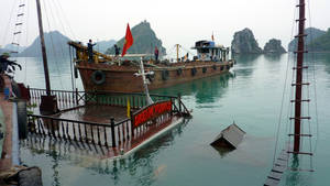Photo -   FILE - In this Feb. 18, 2011 file photo, a tour boat, submerged in the water, is pulled up in the Halong Bay in northern Quang Ninh province, Vietnam, a day after 12 people from nine nations died when their boat sank early in the morning. Each day, up to 10,000 tourists from around the world sail around the bay, a UNESCO-heritage site and one of the country's most visited tourist attractions, and gaze at its stunning limestone pillars and caves. But at least four deadly accidents over the last 10 years and many more alarming safety incidents recounted on traveler's blogs have led to allegations that the ships are cutting corners. (AP Photo/Dinh Tran Trung Hau, File)
