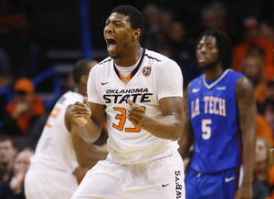 Photo - Oklahoma State guard Marcus Smart (33) celebrates in the first half of an NCAA college basketball game against Louisiana Tech in the All College Classic in Oklahoma City, Saturday, Dec. 14, 2013. Louisiana Tech forward Chris Anderson (5) is at right. (AP Photo/Sue Ogrocki)