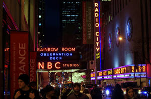 "photo - FILE - In this Friday, Aug. 21, 2009, file photo, the NBC logo glows in neon lights among other iconic signs at its headquarters in New York. Comcast said Tuesday, Feb. 12, 2013, that it's buying General Electric's 49 percent stake in the NBCUniversal joint venture for $16.7 billion several years early, as the company takes advantage of low borrowing costs and what CEO Brian Roberts called a ""very attractive price.""  (AP Photo/Bebeto Matthews, File)"