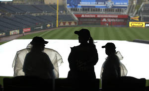 Photo -   Kauffman Stadium ushers take cover as they watch rain fall before a baseball game between the Minnesota Twins and Kansas City Royals Friday, Aug. 31, 2012, in Kansas City, Mo. The game was canceled due to rain and a doubleheader will be played on Saturday. (AP Photo/Ed Zurga)