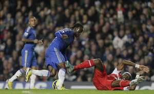 photo - Chelsea's Victor Moses, left, takes the ball past a fallen Queens Park Rangers' Stephane Mbia  during their English Premier League soccer match at Chelsea's Stamford Bridge stadium in London, Wednesday, Jan.  2, 2013. (AP Photo/Alastair Grant)