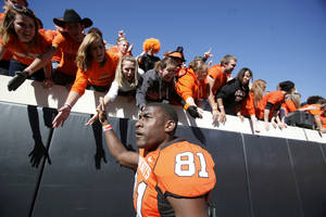 Photo - OSU's Justin Blackmon celebrates with fans during the college football game between the Oklahoma State University Cowboys (OSU) and the Baylor University Bears at Boone Pickens Stadium in Stillwater, Okla., Saturday, Nov. 6, 2010. Photo by Sarah Phipps, The Oklahoman
