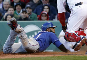 Photo - Texas Rangers' Elvis Andrus slides into home to score on a sacrifice fly hit by Alex Rios in the eighth inning of a baseball game against the Boston Red Sox at Fenway Park in Boston, Wednesday, April 9, 2014. (AP Photo/Elise Amendola)