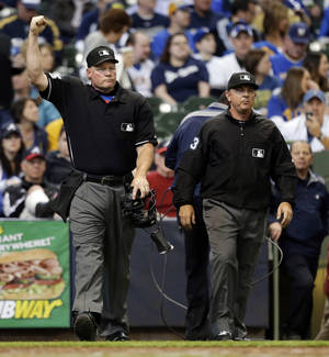 Photo - Umpire Ted Barrett, left, signals an out call after listening to the central replay booth in New York in the sixth inning of an opening day baseball game between the Atlanta Braves and Milwaukee Brewers, Monday, March 31, 2014, in Milwaukee. An umpire's call has been overturned for the first time under Major League Baseball's expanded replay system, with Brewers' Ryan Braun ruled out instead of safe. (AP Photo/Jeffrey Phelps)