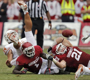 Photo - OU's Tom Wort (21) and Tony Jefferson (1) force a fumble on UT's David Ash (14) during the Red River Rivalry college football game between the University of Oklahoma (OU) and the University of Texas (UT) at the Cotton Bowl in Dallas, Saturday, Oct. 13, 2012. Photo by Chris Landsberger, The Oklahoman
