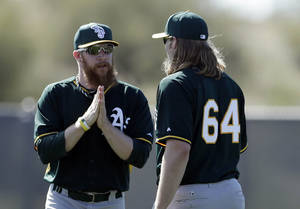 Photo - Oakland Athletics pitcher Sean Doolittle, left, talks with pitcher A.J. Griffin during spring training baseball practice on Saturday, Feb. 15, 2014, in Scottsdale, Ariz. Doolittle is scheduled to be held out of bullpen sessions for few days because of a right calf strain, according to Athletics manager Bob Melvin. (AP Photo/Gregory Bull)