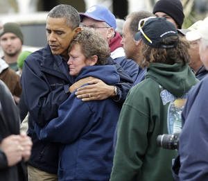 Photo -   President Barack Obama, left, embraces Donna Vanzant, right, during a tour of a neighborhood effected by superstorm Sandy, Wednesday, Oct. 31, 2012 in Brigantine, N.J. Vanzant is a owner of North Point Marina, which was damaged by the storm. (AP Photo/Pablo Martinez Monsivais)