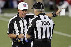 Photo -   Referee Craig Ochoa, left, talks with field judge Rusty Spindel (105) during the first quarter of the NFL Hall of Fame exhibition football game between the Arizona Cardinals and New Orleans Saints, Sunday, Aug. 5, 2012 in Canton, Ohio. (AP Photo/Gene J. Puskar)