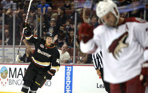 Photo - Anaheim Ducks defenseman Hampus Lindholm, left, celebrates his goal as Phoenix Coyotes center Kyle Chipchura looks on during the second period of their preseason NHL hockey game, Monday, Sept. 16, 2013, in Anaheim, Calif.  (AP Photo/Mark J. Terrill)