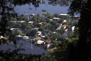 Photo - CORRECTS SPELLING OF LAMBARE -  Homes are surrounded by floodwater in the Cateura neighborhood, seen from Lambare Hill in Asuncion, Paraguay, Tuesday, June 10, 2014. Thousands of people living along the Paraguay River have been affected by flooding after the river overflowed its banks. (AP Photo/Jorge Saenz)