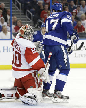 Photo - Tampa Bay Lightning center Alex Killorn (17) attempts to deflect the puck past Detroit Red Wings goalie Jonas Gustavsson (50), of Sweden, during the second period of an NHL hockey game on Thursday, Dec. 12, 2013, in Tampa, Fla. (AP Photo/Chris O'Meara)