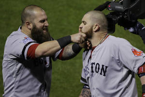 Photo - Boston Red Sox Mike Napoli, right, pulls Jonny Gomes' beard after Gomes hit a three run home run off of St. Louis Cardinals relief pitcher Seth Maness, left, during the sixth inning of Game 4 of baseball's World Series Sunday, Oct. 27, 2013, in St. Louis.(AP Photo/Charlie Neibergall)