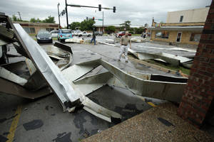 Photo - Above: The roof of a strip mall at Gray Street and Webster Avenue lies in a parking lot on April 13 after a tornado forged a path through Norman.