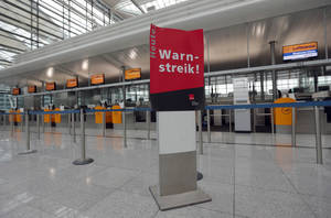 Photo - Empty counters and a poster that reads ' Warning Strike' is seen during a warning strike of employees of the German airliner Lufthansa at the airport in Munich, southern Germany, Monday, April 22, 2013. (AP Photo/Matthias Schrader)