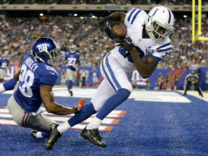 Photo - Indianapolis Colts wide receiver T.Y. Hilton (13) catches a pass for a touchdown in front of New York Giants' Jayron Hosley (28) during the first half of an NFL preseason football game Sunday, Aug. 18, 2013, in East Rutherford, N.J. (AP Photo/Kathy Willens)