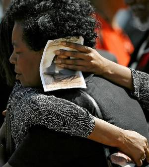Photo - Mourners embrace outside the Greater New Zion Baptist Church following the funeral of Pastor Carol Daniels today. Photo by John Clanton