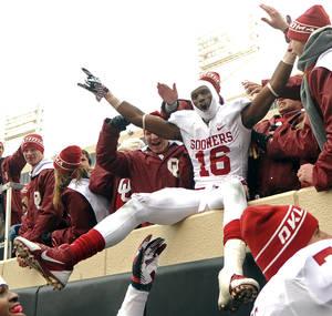 Photo - Oklahoma Wide Receiver Jaz Reynolds celebrates with fans after their 34-24 win over Oklahoma State in an NCAA college football game in Stillwater, Okla., Saturday, Dec. 7, 2013. (AP Photo/Brody Schmidt)