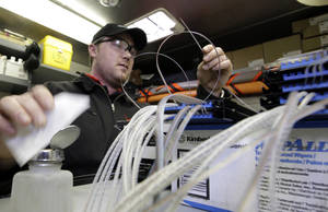 Photo -  Todd Torbert, a Verizon cable splicing technician, works to connect the glass fibers to the Verizon FiOS fiber network in Rockville, Md.  AP File Photos  <strong>Alex Brandon -  AP </strong>